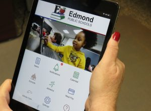 Mobile device being held up showing the Edmond Public School new mobile app