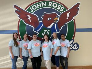 Our Cafe staff standing in front of the John Ross nighthawk , painted on the wall in the cafeteria.